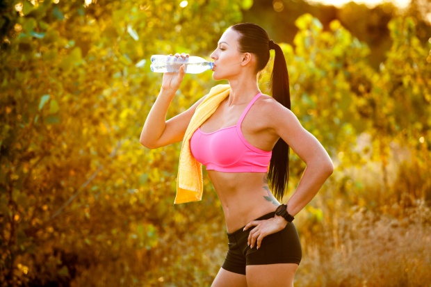 Athlete  with bottle of water after running workout outdoors